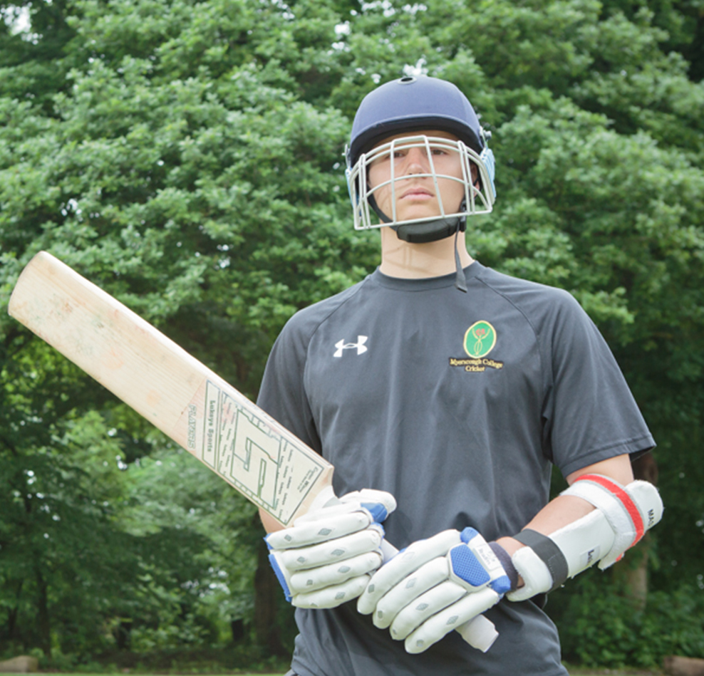 Myerscough Cricket student holding a cricket bat and wearing protective pads