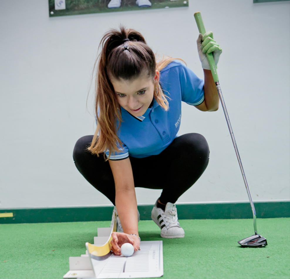 Myerscough College student lines up a golf ball on a practice putting green